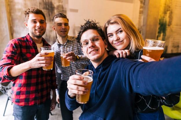 Pareja joven tomando selfie con sus amigos sosteniendo los vasos de cerveza