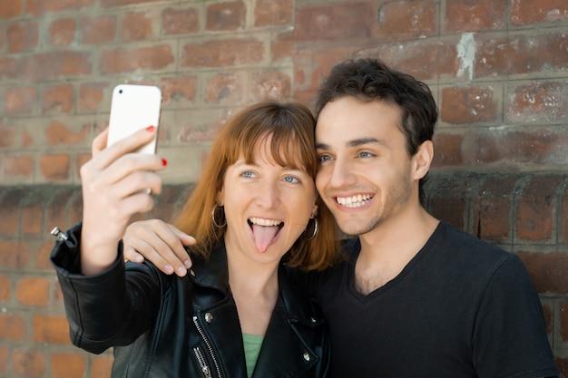 Pareja joven tomando selfie con teléfono móvil al aire libre.