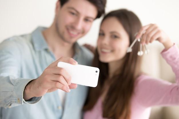 Pareja joven tomando selfie usando teléfono inteligente sosteniendo las llaves