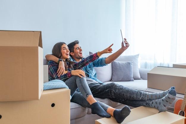 Pareja joven tomando selfies con su tableta en su nuevo hogar
