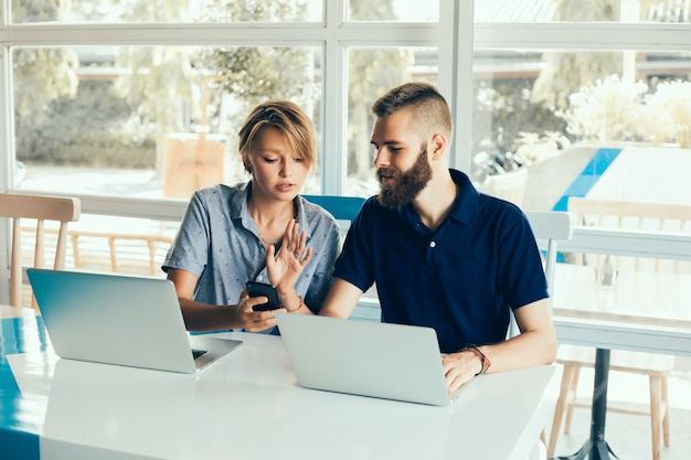 Pareja joven trabajando en computadoras portátiles en un café haciendo un proyecto, conferenciando, freelancers