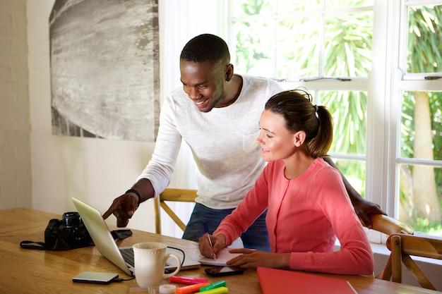 Pareja joven trabajando juntos en una computadora portátil