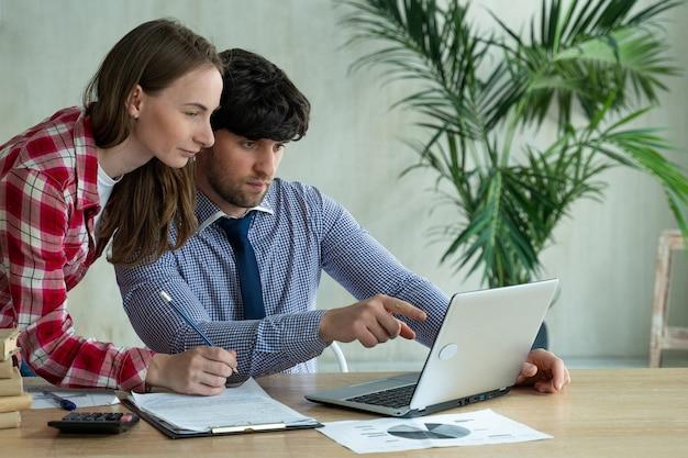 Pareja joven trabajando juntos en la oficina joven apuntando a la computadora portátil con una sonrisa y discutiendo algo con su compañero de trabajo