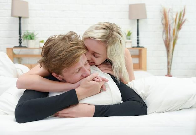 Pareja joven tumbado en la cama juntos. pareja romántica en el amor mirando el uno al otro.