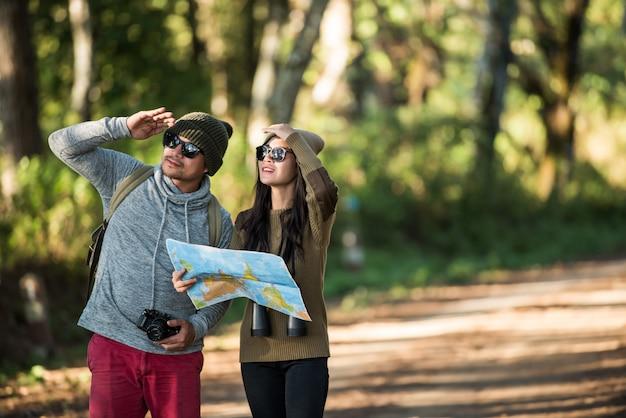 Pareja joven turista viaja en bosque de montaña