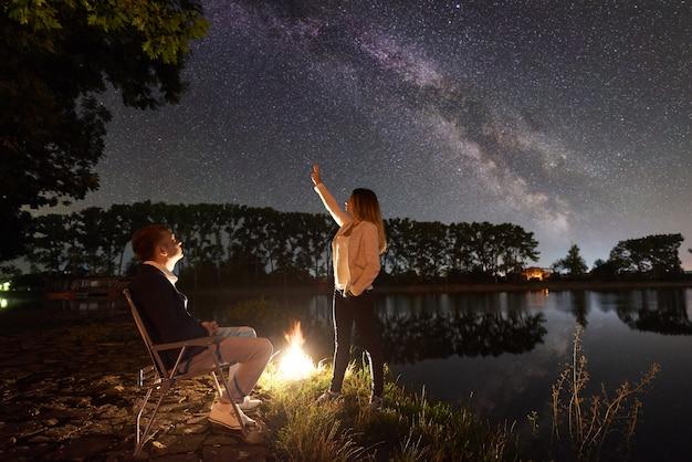 Pareja joven turistas descansando cerca de la hoguera en una orilla del río. hombre sentado en una silla, mujer apuntando al cielo nocturno lleno de estrellas