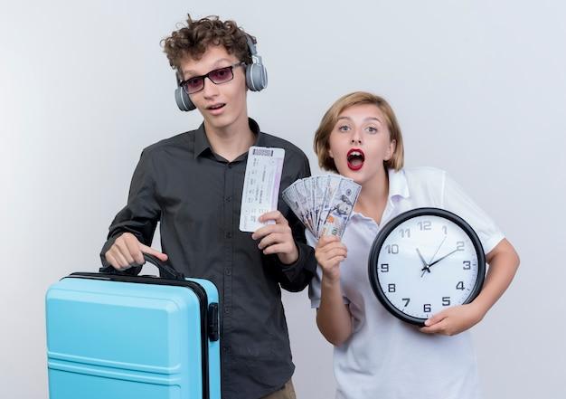 Pareja joven de turistas hombre con auriculares sosteniendo maleta y billetes de avión junto a su novia con dinero en efectivo y reloj de pared sorprendido sobre blanco