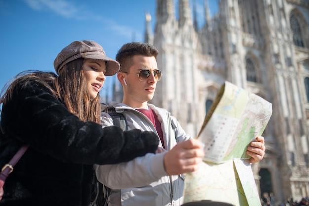 Pareja joven de turistas sosteniendo un mapa en milán, italia