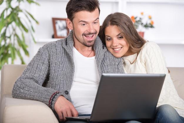 Pareja joven usando una computadora portátil en casa.