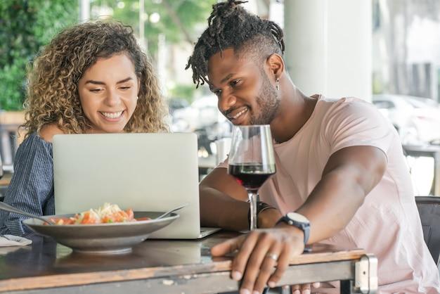 Pareja joven usando una computadora portátil mientras almuerzan juntos en un restaurante.
