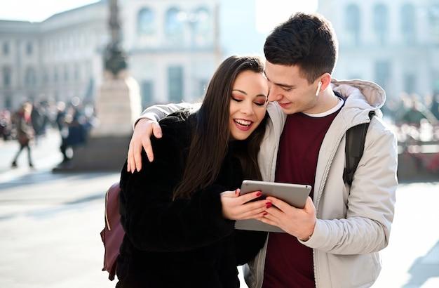Pareja joven usando una tableta digital al aire libre mientras visitaba una ciudad