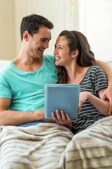 Pareja joven usando tableta digital en el sofá en casa