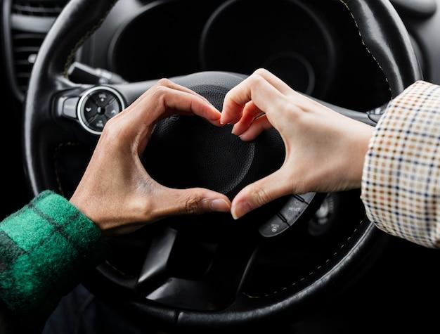 Pareja joven viajando con coche de cerca haciendo forma de corazón