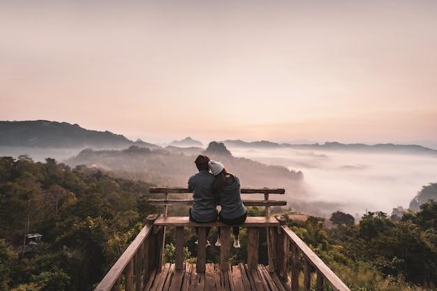 Pareja joven viajero mirando el mar de niebla y puesta de sol sobre la montaña en mae hong son, tailandia