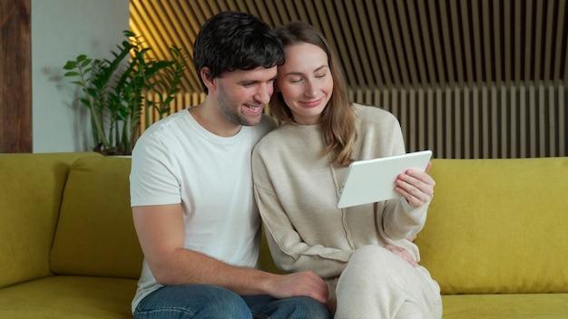Pareja joven viendo contenido multimedia en línea en una tableta sentado en un sofá en casa