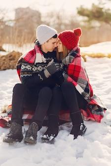 Pareja joven vistiendo una manta en un campo cubierto de nieve