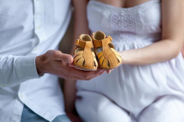Pareja joven con zapatos de bebé sentado en casa