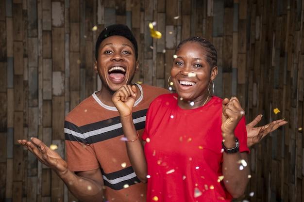 Pareja de jóvenes africanos masculinos y femeninos celebrando con confeti flotando alrededor
