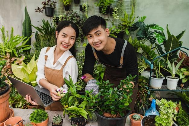 Pareja de jóvenes jardineros asiáticos con delantal usa equipo de jardín y computadora portátil para investigar y cuidar las plantas de la casa en invernadero