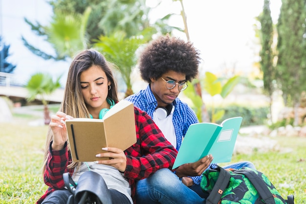 Pareja de jóvenes sentados juntos en el césped leyendo un libro en el parque al aire libre