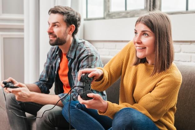 Pareja de jóvenes sentados en el sofá disfrutando jugando al videojuego