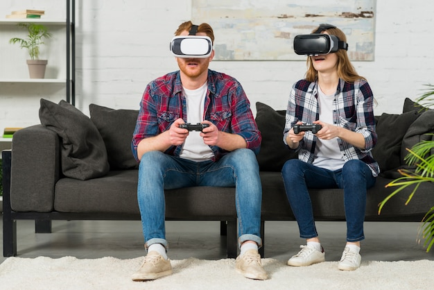 Pareja de jóvenes sentados en el sofá con gafas de realidad virtual jugando al videojuego con joystick