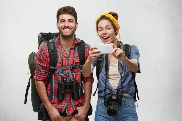 Pareja de jóvenes turistas con equipo