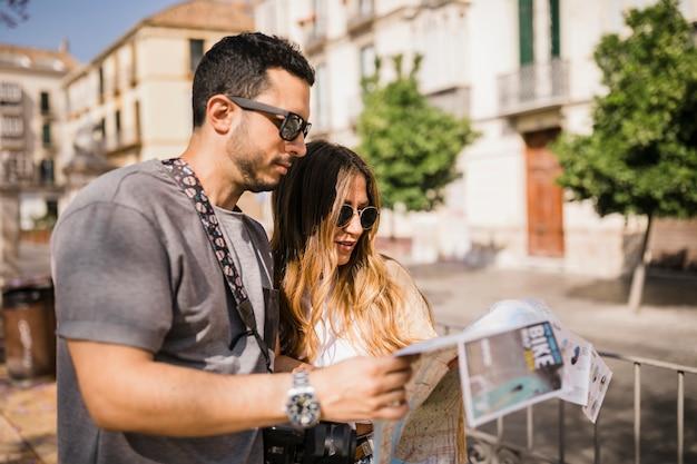 Pareja de jóvenes turistas con estilo mirando el mapa