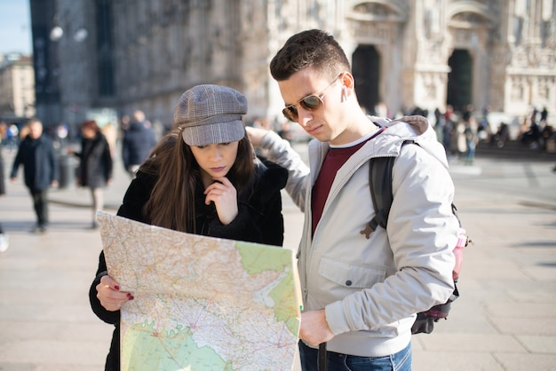 Pareja de jóvenes turistas sosteniendo un mapa en milán, italia