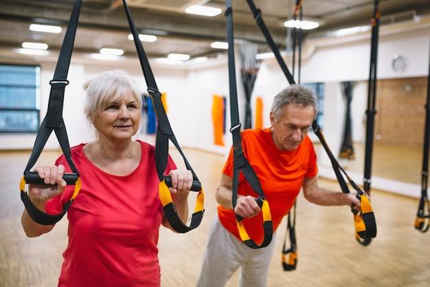 Pareja jubilada entrenando en gimnasio