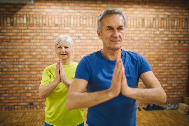 Pareja jubilada meditando en gimnasio