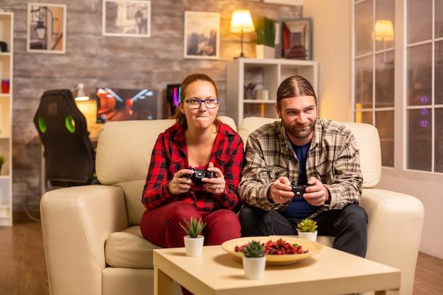 Pareja de jugadores jugando videojuegos en la tv con controladores inalámbricos en las manos.
