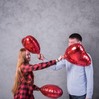 Pareja jugando con globos de corazón