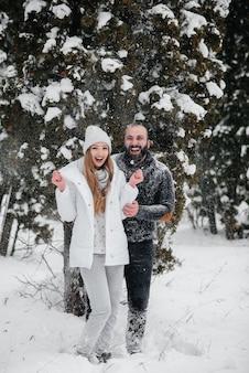 Pareja jugando con nieve en el bosque