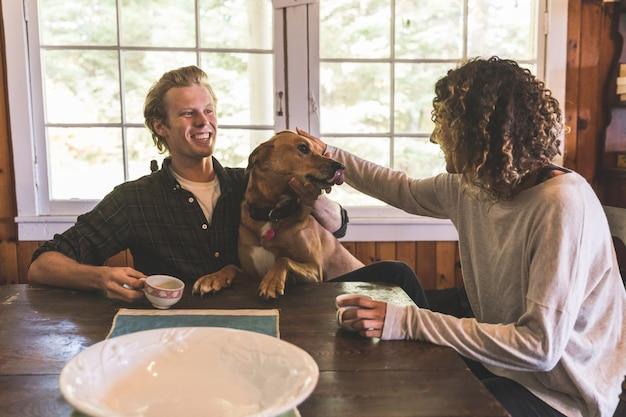 Pareja jugando con un perro en una cabaña