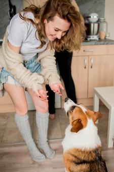 Pareja jugando con perro en casa