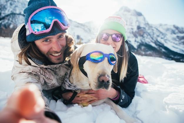Pareja jugando con perro en las montañas, en el suelo nevado