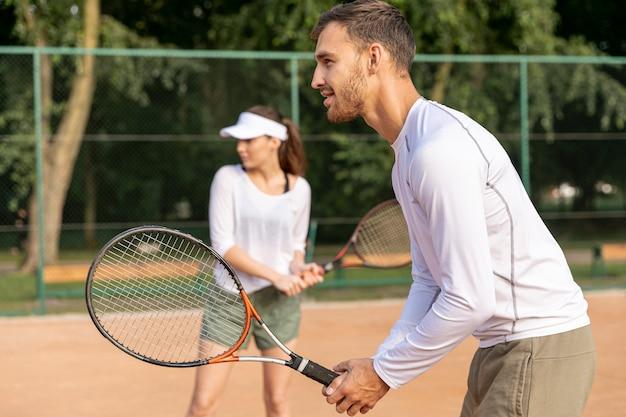 Pareja jugando tenis en dúo