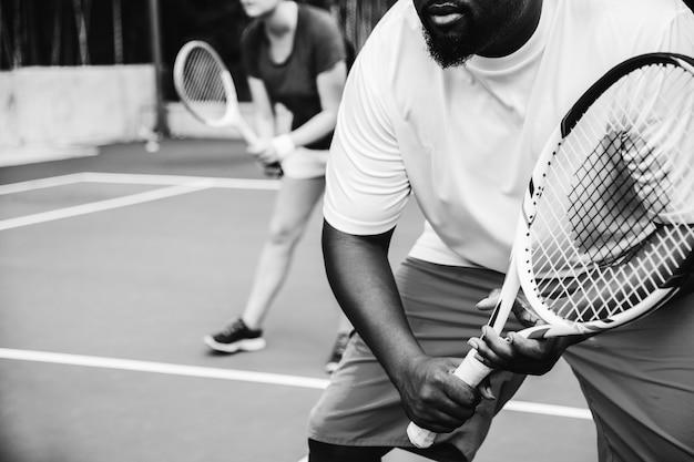 Pareja jugando tenis en equipo
