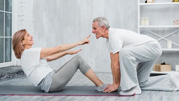 Pareja juguetona haciendo ejercicio de yoga en casa