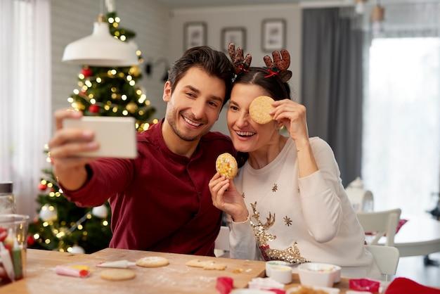 Pareja juguetona haciendo un selfie en navidad