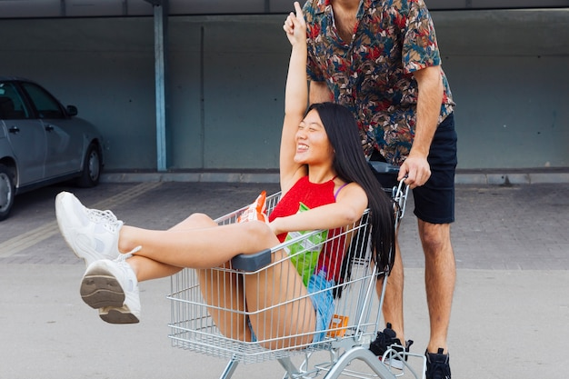 Pareja juguetona montando en carrito de compras