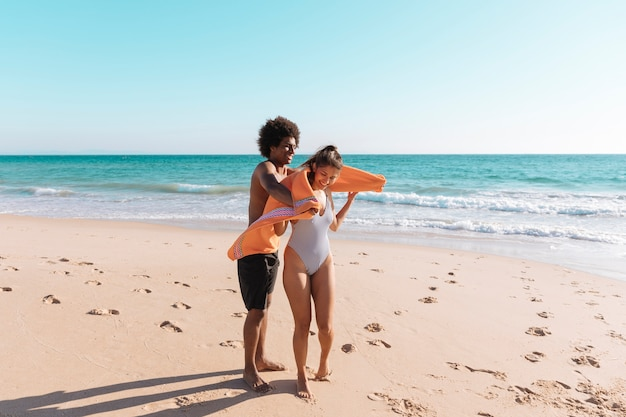 Pareja juguetona multiétnica en la playa
