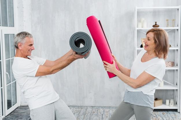 Pareja juguetona senior peleando con rollo de yoga mat