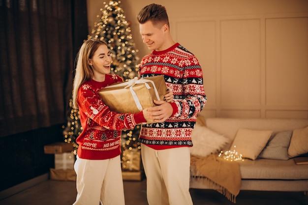Pareja junto con regalos de navidad por el árbol de navidad