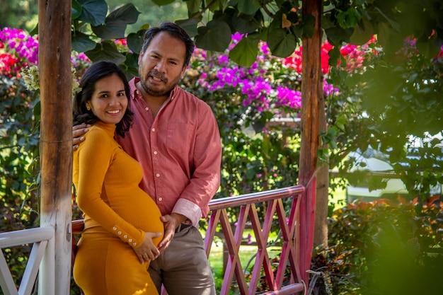 Pareja latinoamericana esperando un bebé en un hermoso parque lleno de flores.