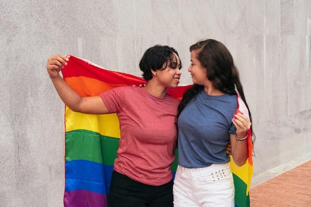 Pareja de lesbianas con bandera lgtb en la ciudad. concepto lgbt