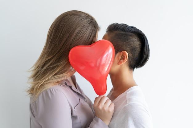 Pareja de lesbianas besándose detrás de un globo en forma de corazón
