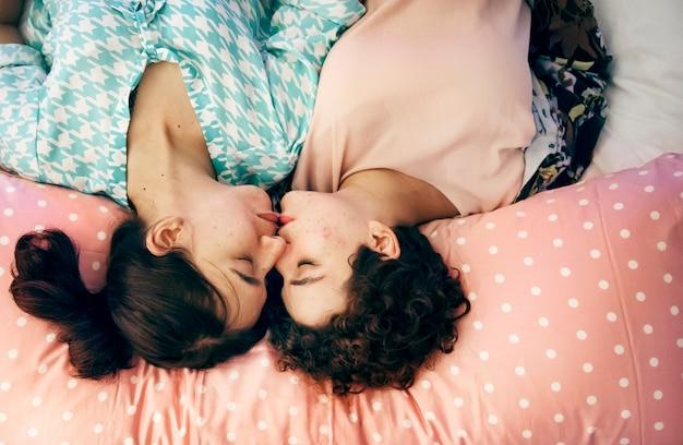 Pareja de lesbianas durmiendo en la cama juntos