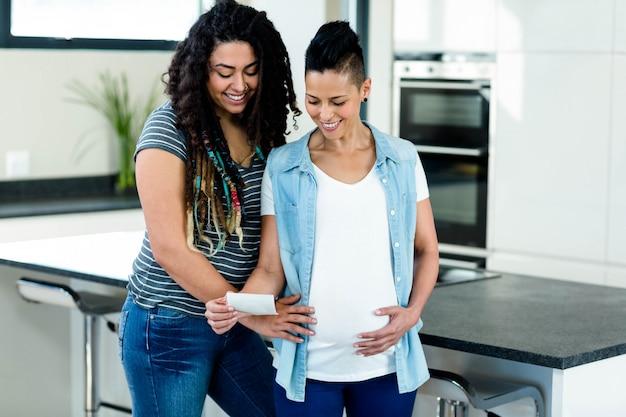 Pareja de lesbianas embarazadas mirando el informe de sonografía y sonriendo en la cocina